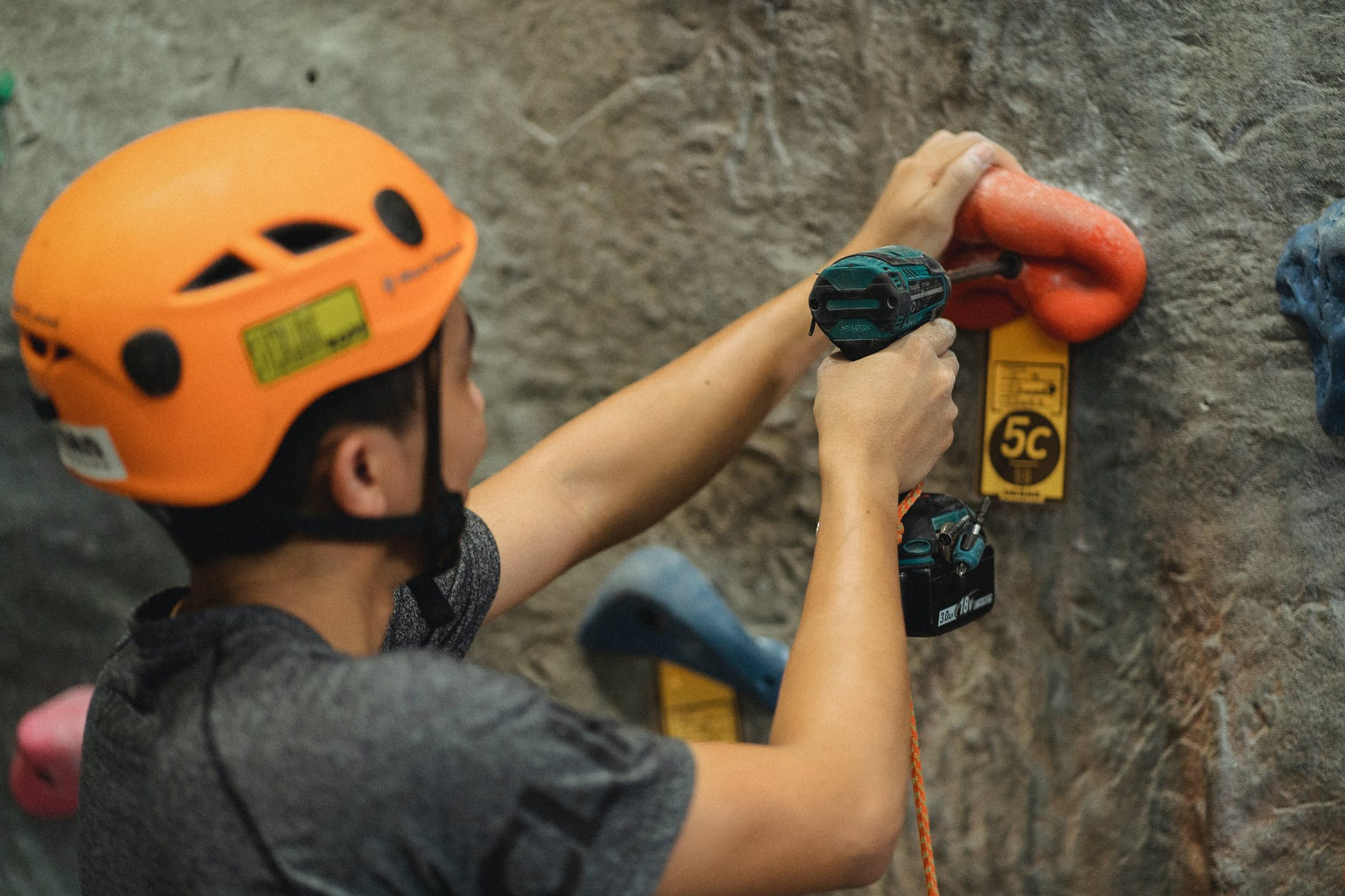 crop athlete fasten climbing hold with screwdriver on wall in gym